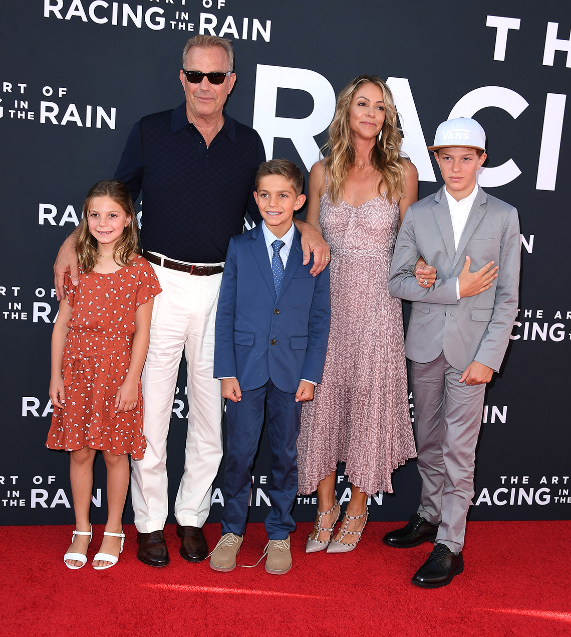 kevin costner his wife christine baumgartner and their three kids stand on the red carpet at an event