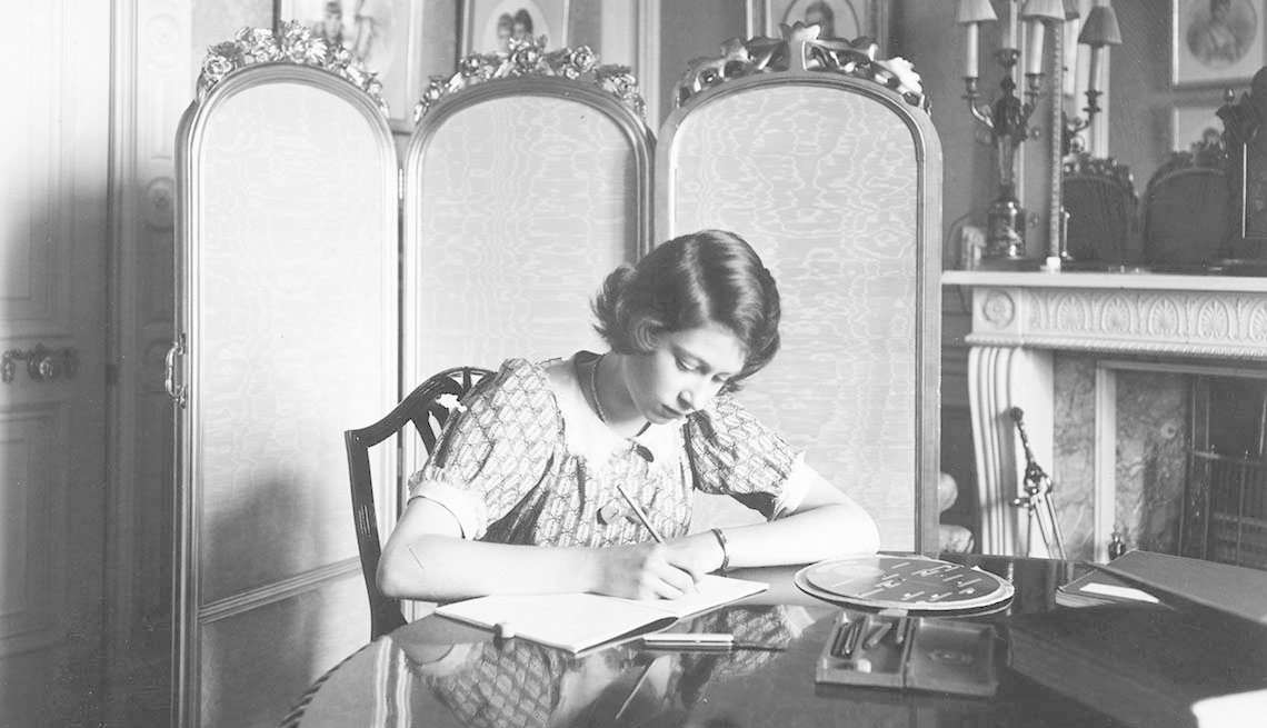item 2 of Gallery image - Princess Elizabeth writing in a notebook at a desk in Windsor Castle