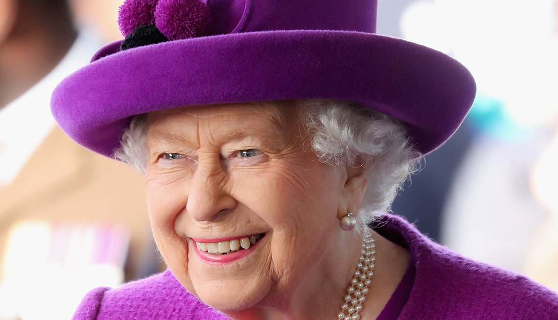 Queen Elizabeth II wearing a purple hat smiling as she visits the Royal British Legion Industries village