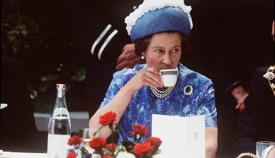 item 1 of Gallery image - Queen Elizabeth ll drinking a cup of tea during a 1977 royal visit in Northern Ireland