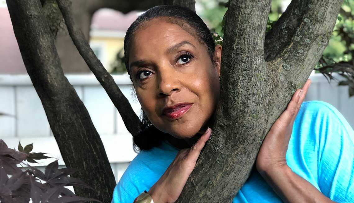 Actress Phylicia Rashad leans on a tree posing for photo