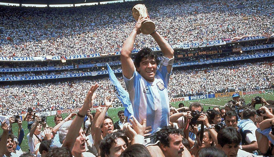 Diego Armando Maradona sosteniendo la Copa Mundial y en los hombros de los fanáticos, México, 1986