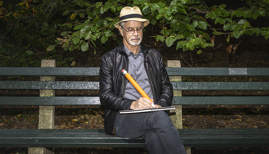 photo of garry trudeau sitting on a park bench with an oversized pencil in hand drawing a cartoon