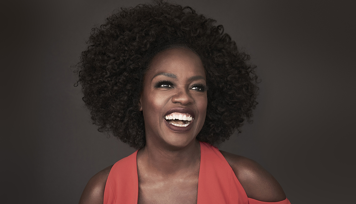 closeup of viola davis smiling during a photo shoot wearing a red jumpsuit