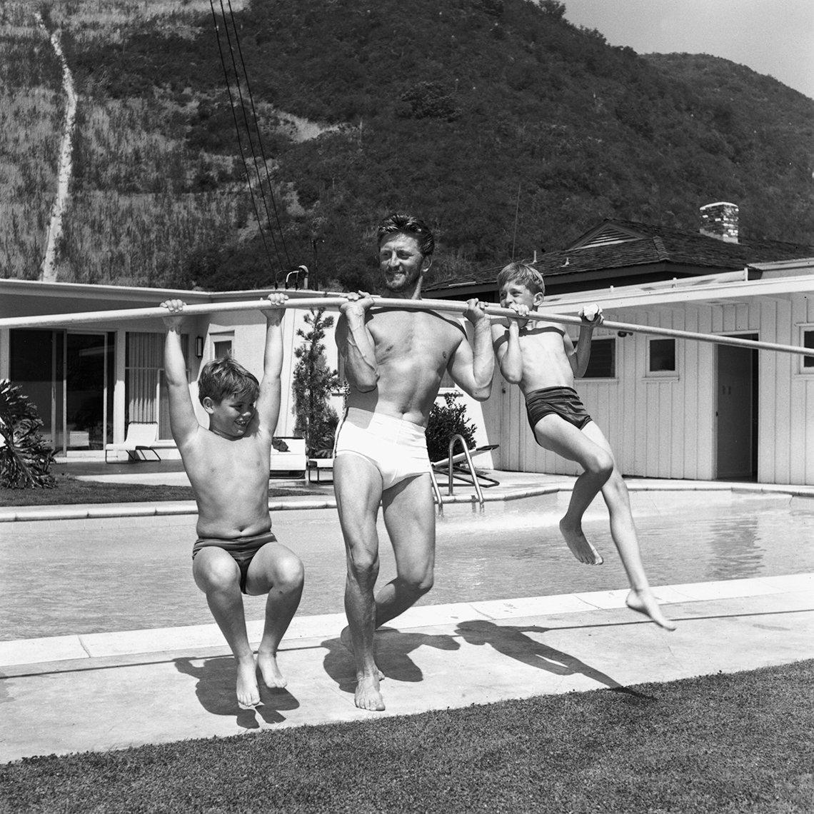 Foto en blanco y negro de los años 50 de Kirk Douglas levantando a sus hijos Michael y Joel con una vara frente a una piscina.