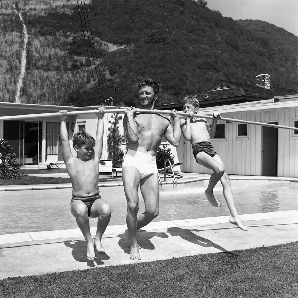 black and white photo from the fifties showing actor kirk douglas lifting his sons michael and joel up in his backyard using a pole