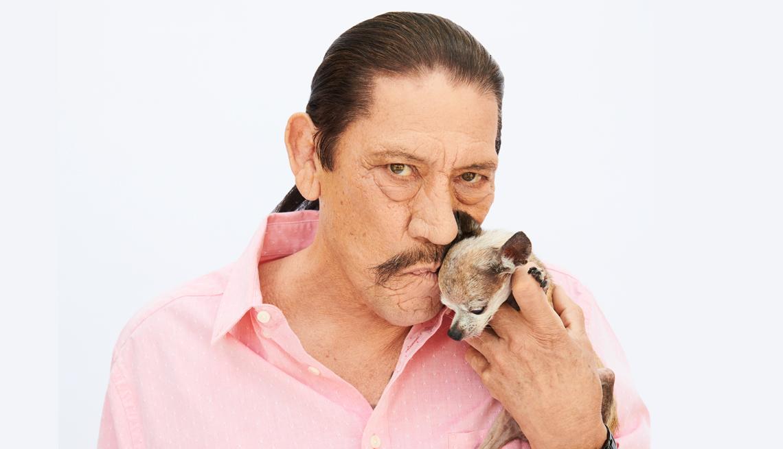 El actor Danny Trejo sosteniendo un chihuahua.