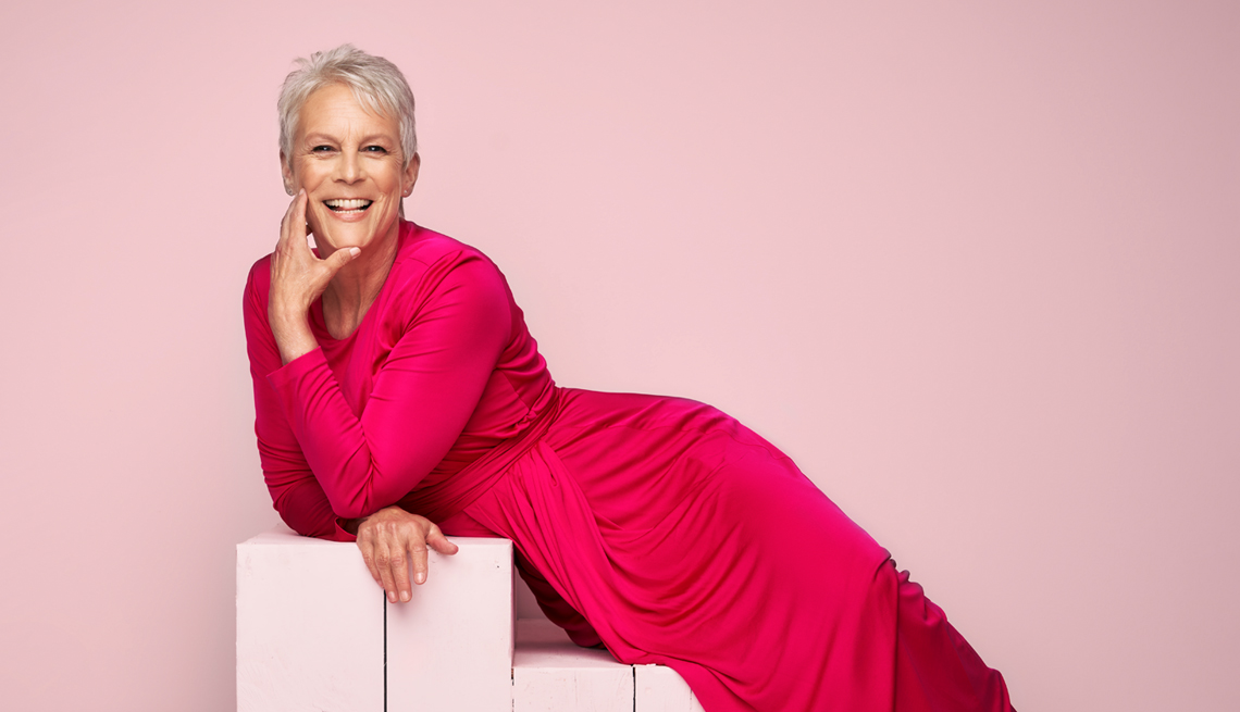 actress jamie lee curtis in a hot pink dress laying on light pink stairs