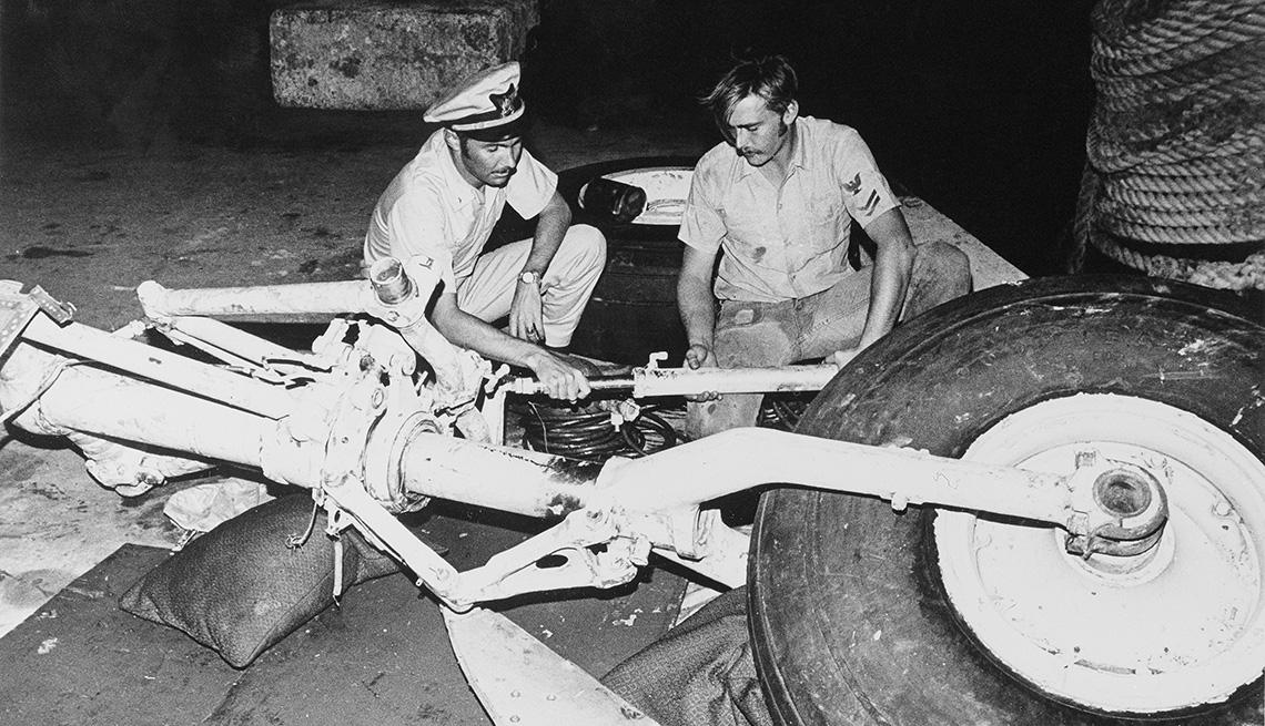 item 8 of Gallery image - Dos funcionarios inspeccionan los restos del avión que que transportaba a Roberto Clemente y otras cuatro personas que se estrelló en el Océano Atlántico frente a las costas de Puerto Rico.