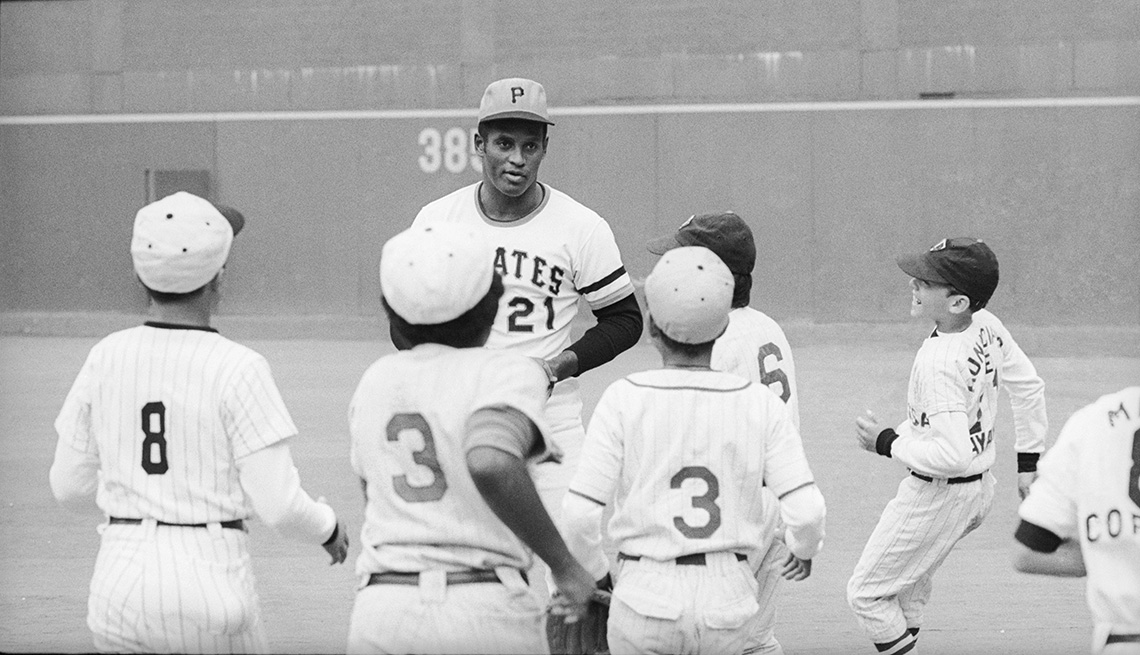 item 6 of Gallery image - Roberto Clemente at Three Rivers Stadium in Pittsburgh with a group of youngsters from Puerto Rico in baseball uniforms