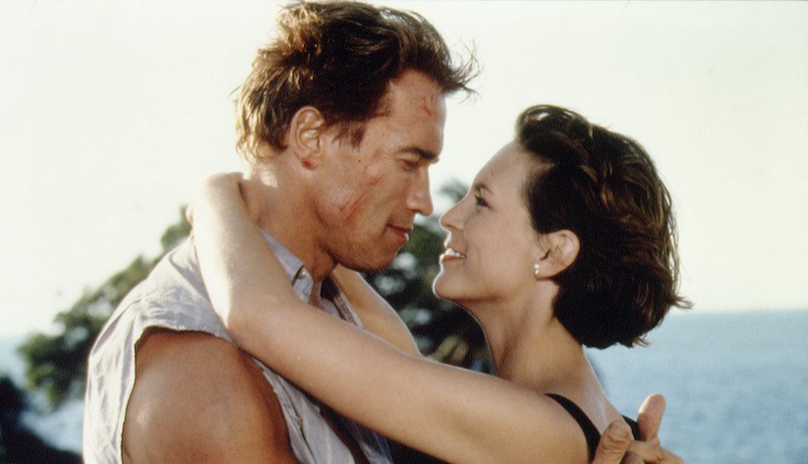 Arnold Schwarzenegger and Jamie Lee Curtis embrace in the film True Lies