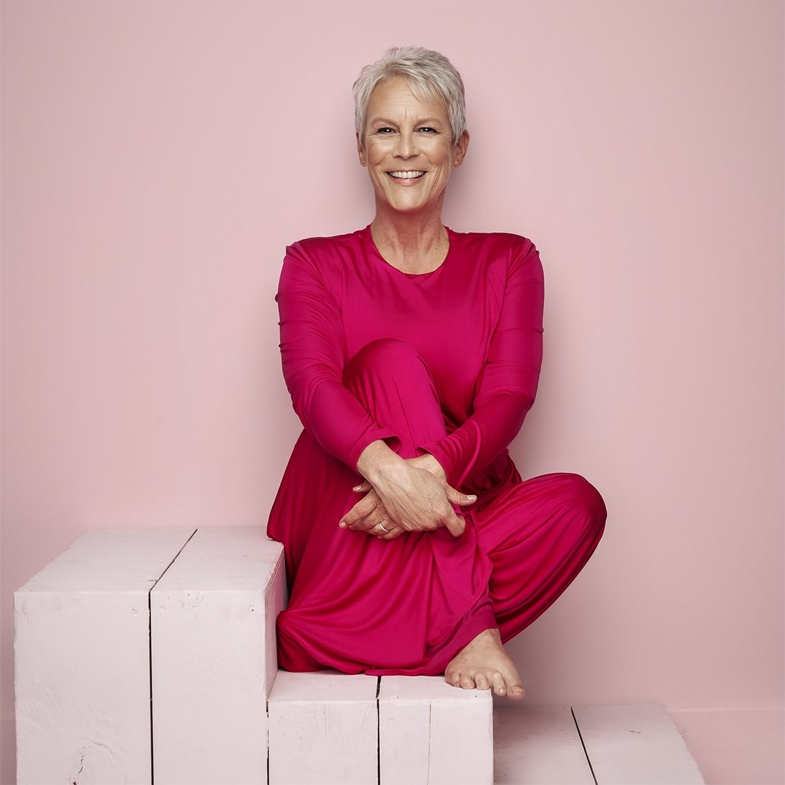 actress jamie lee curtis casually seated in a red dress