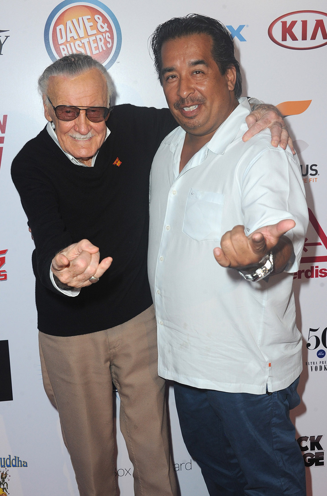 stan lee and max anderson holding out their hands like spider-man shooting out his web