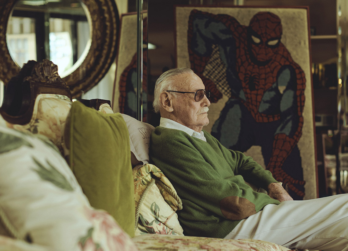 Stan Lee sits on the couch of his home with spider man picture in background
