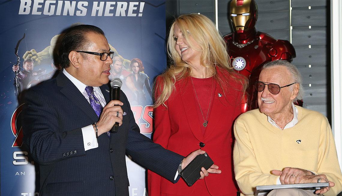 El publicista Jerry Olivarez sostiene el micrófono mientras J.C. Lee y Stan Lee miran.