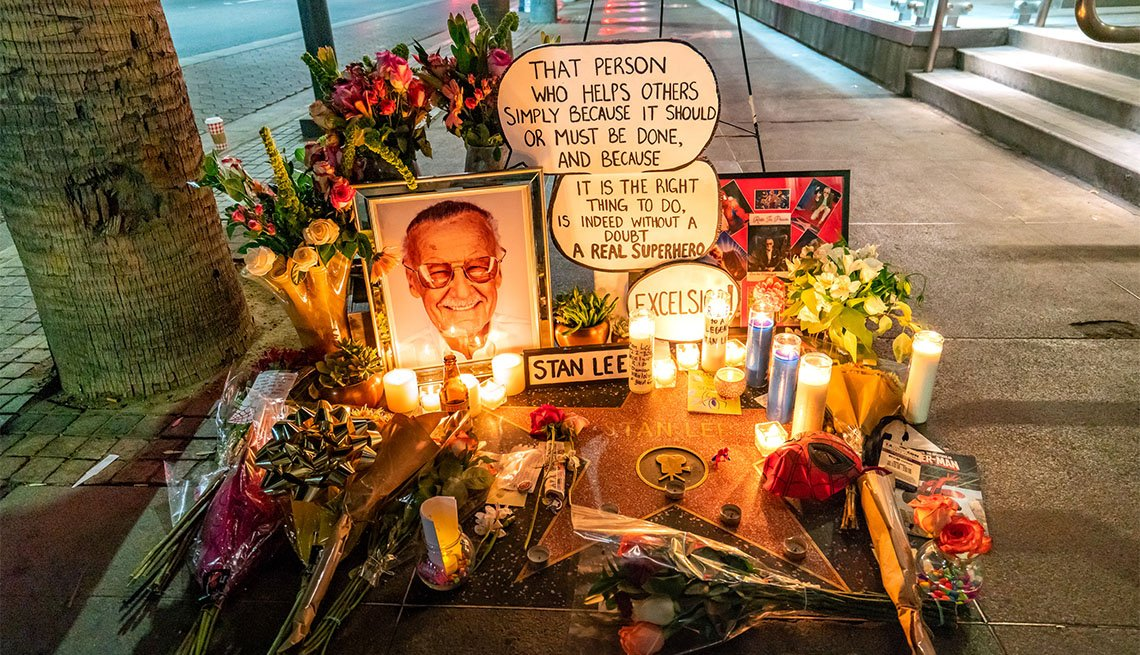 candles and flowers and picture of stan lee on sidewalk memorial