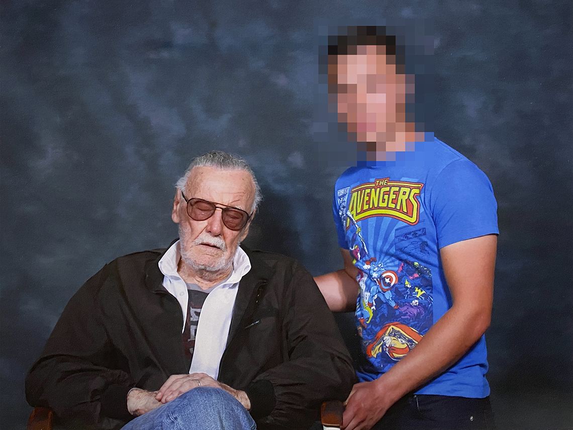 stan lee sits in chair sleeping next to a fan during a photo op