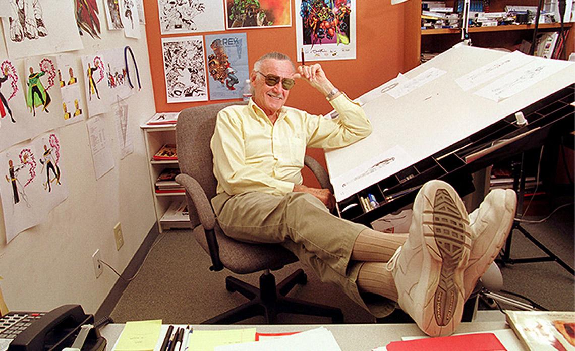 Stan Lee apoyado en su mesa de dibujo en su oficina.