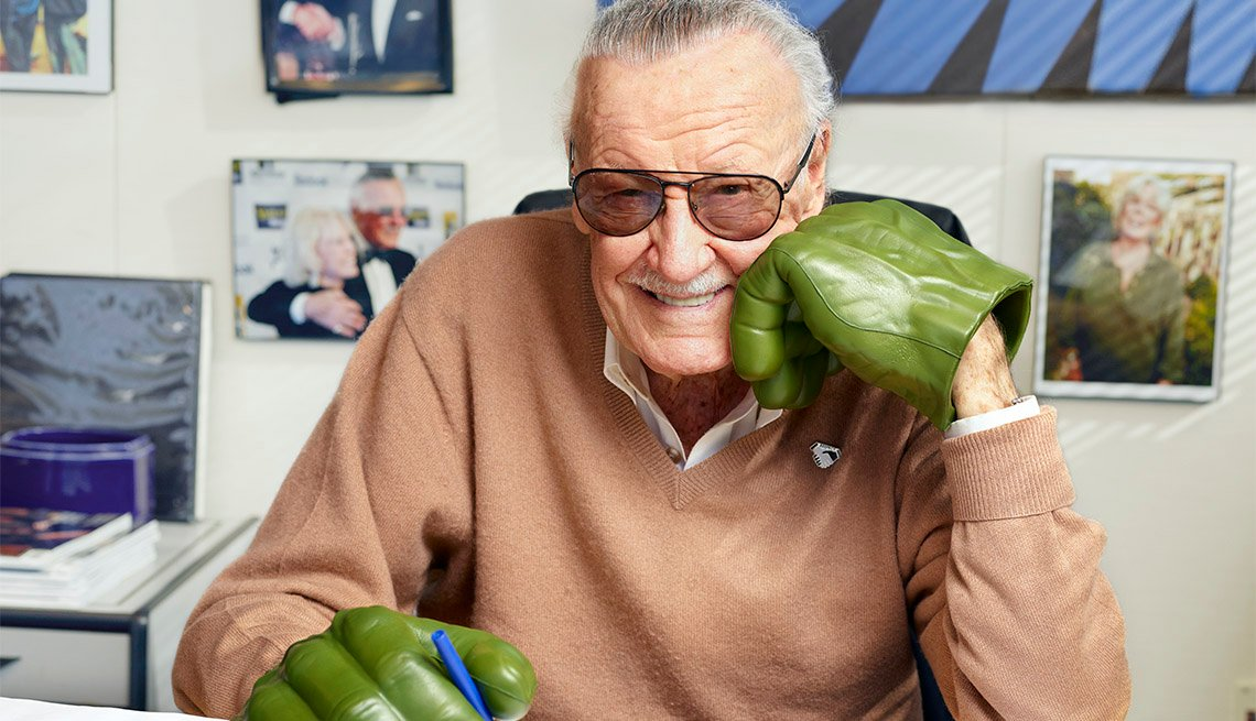 stan lee smiles at his desk holding a pen wearing green hulk gloves
