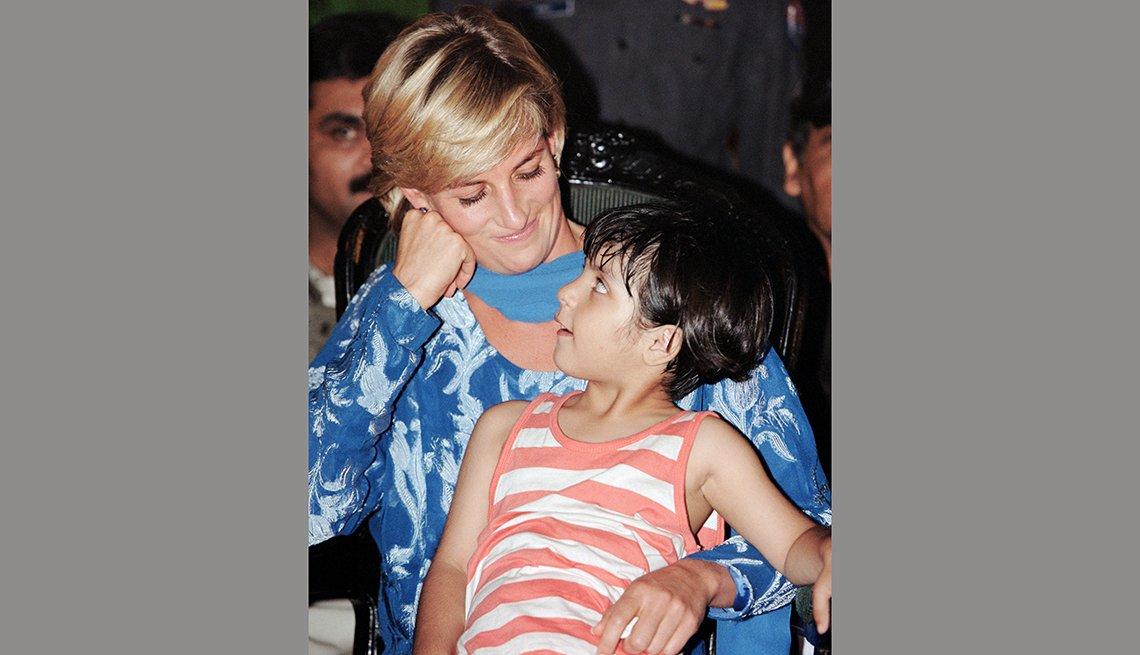 Princesa Diana con un niño sentado en sus piernas