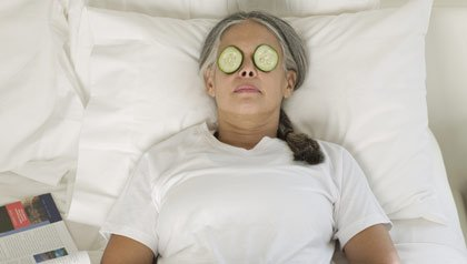 Asian woman with cucumber slices on eyes