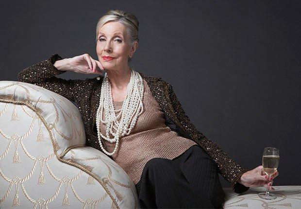 Mujer mayor sentada en un sofá con una copa de vino - Consejos de moda para mayores de 50