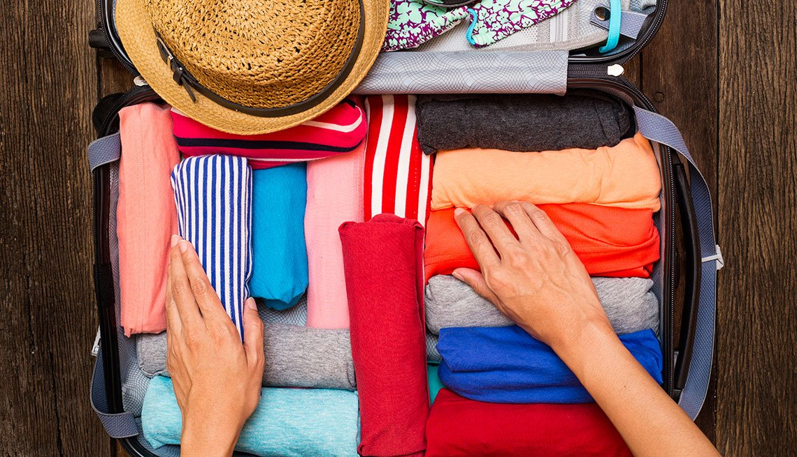mature woman organizing colorful clothes in a suitcase