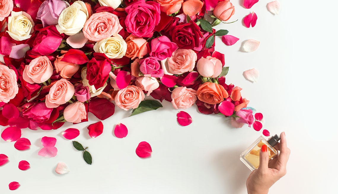 Women's hand spraying mist of rose in mid-air on white background