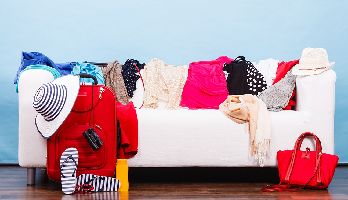 Clothes on a couch next to a carry on suitcase
