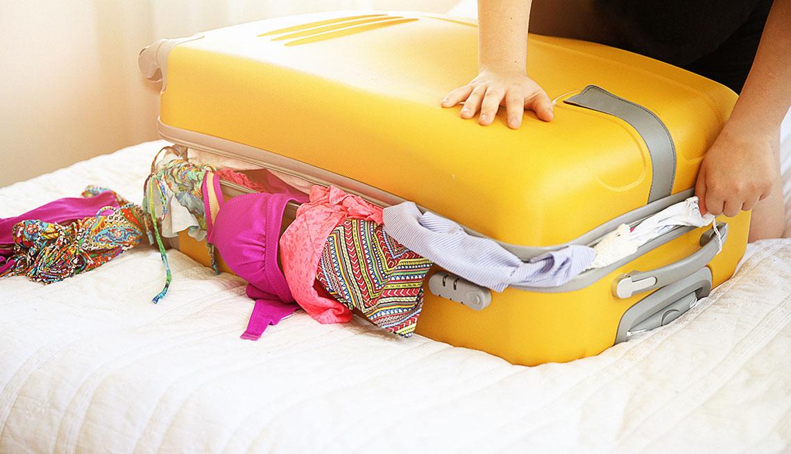 Mujer tratando de cerrar una maleta con ropa que se sale.