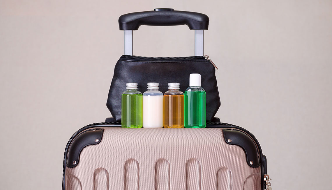 sample size shampoo and creams lined up on top of a carry on suitcase