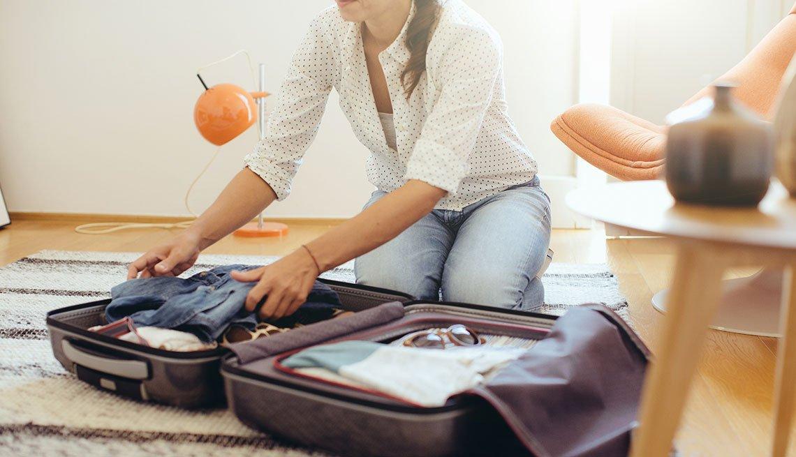 Mujer empacando en una maleta de mano