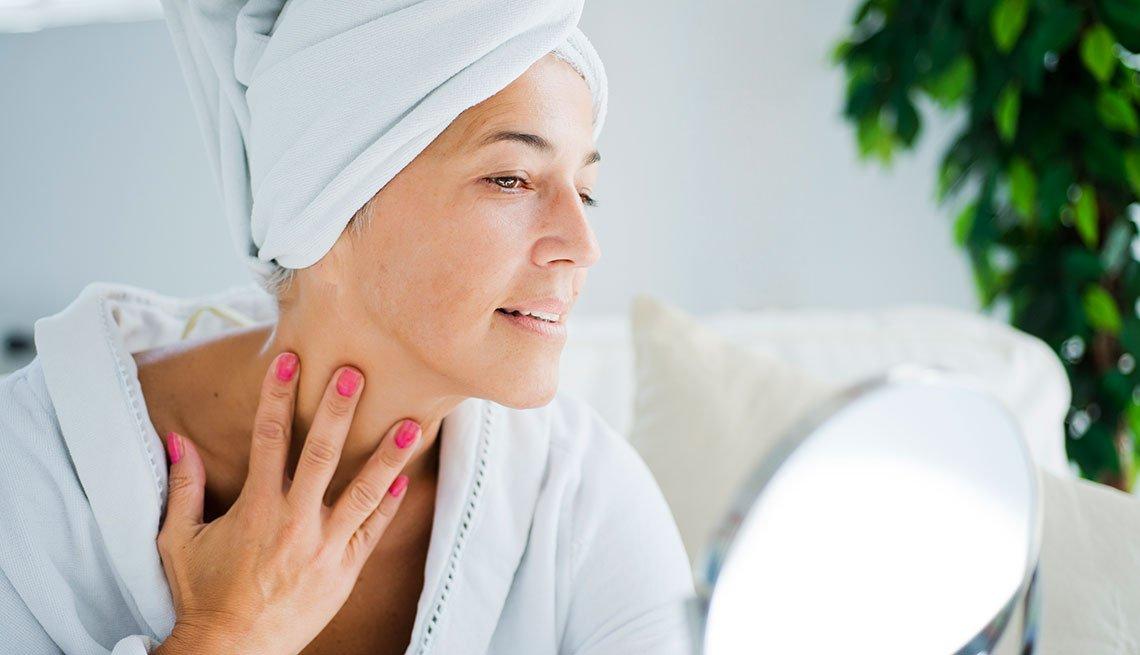 Mujer en bata de baño revisando su cuello