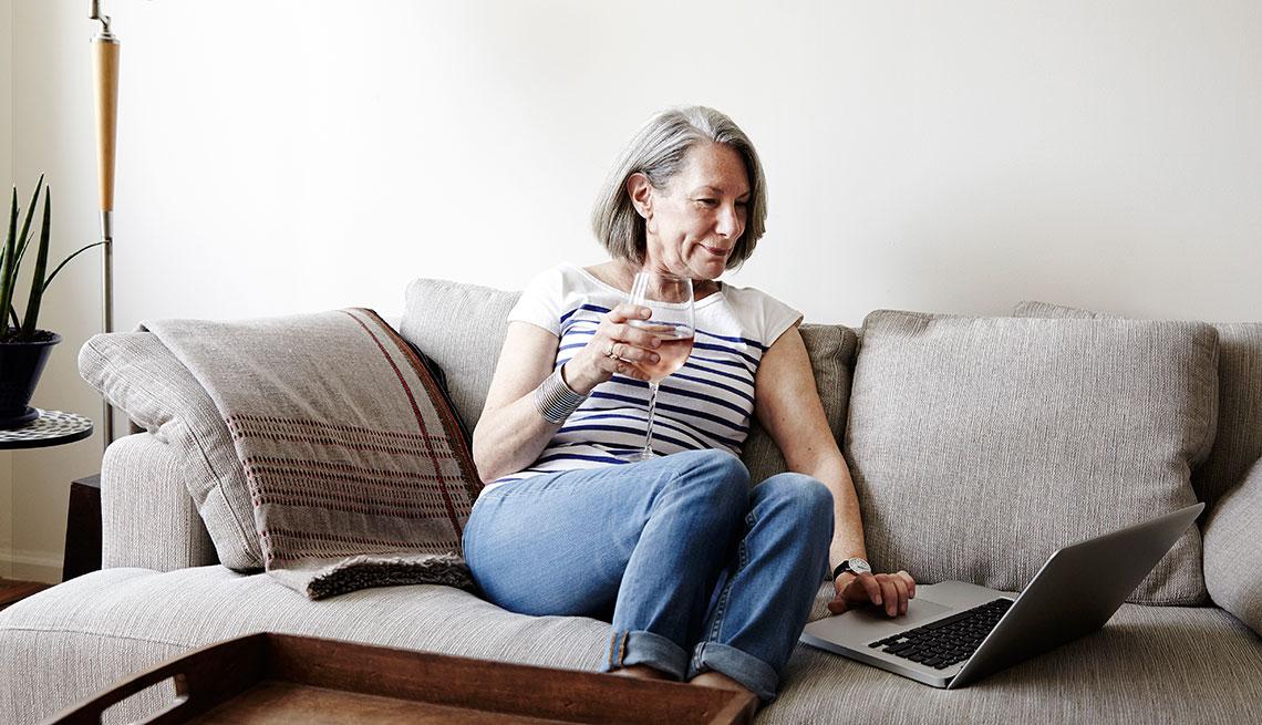 Mujer mayor sentada en una sofa con una copa en la mano y viendo un computador portátil