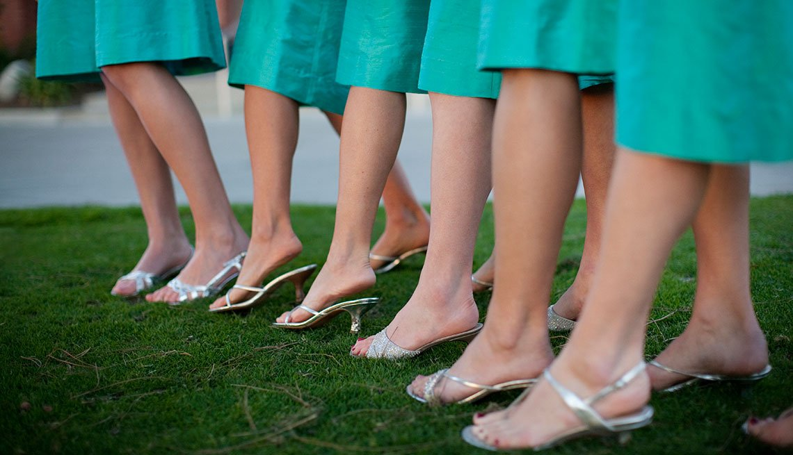 Bride's mainds dressed in green lined up while standing on grass