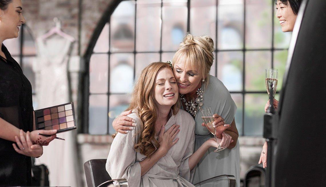Novia preparándose para la boda y recibiendo un abrazo de su madre