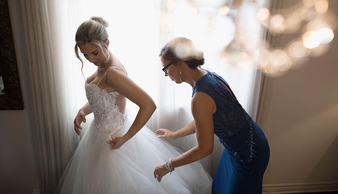 Mujer vestida de novia con su madre arreglando el vestido