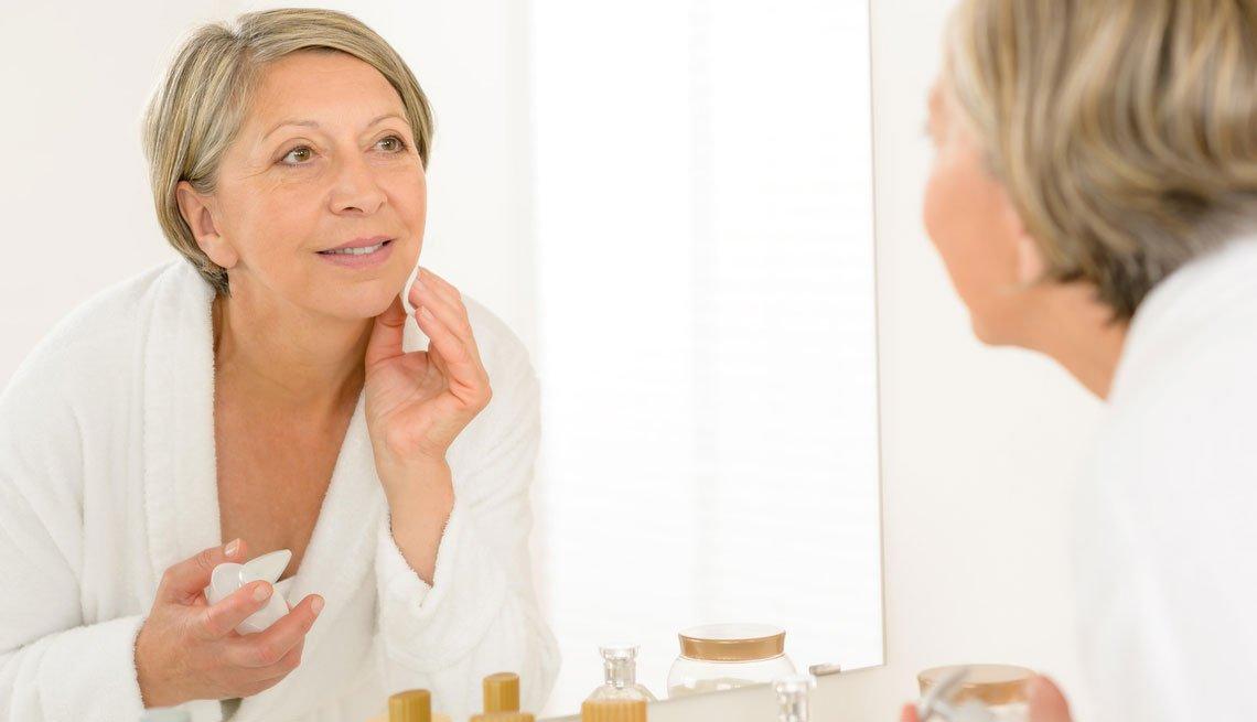 Mujer mayor limpiándose la cara frente a un espejo.