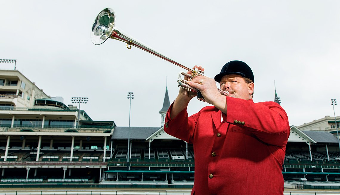 A man in red coat and black hat blowing a bugle at Churchill Downs