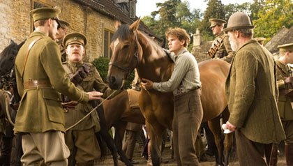 Albert (Jeremy Irvine, center) holds on to Joey defiantly while his father (Peter Mullan, right) looks on in this scene from DreamWorks Pictures'