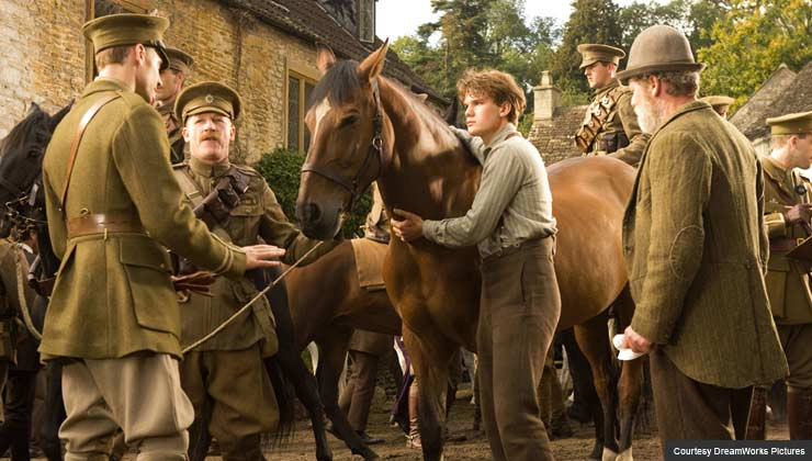 """Albert (Jeremy Irvine, center) holds on to Joey defiantly while his father (Peter Mullan, right) looks on in this scene from DreamWorks Pictures' """"War Horse""""."""