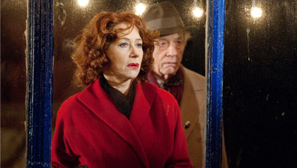 Brighton Rock Movie Review - Helen Mirren, as Ida, looks out behind a window with John Hurt, as Phil Corkery, beside her.