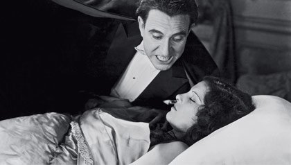 Carlos Villarias, como Drácula, se inclina sobre Lupita Tovar.