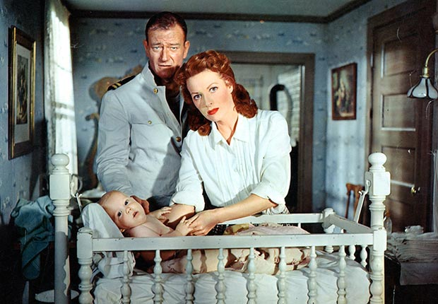 John Wayne and Maureen O'Hara stand over a baby in a crib in a scene from the film 'The Wings Of Eagles', 1957. For best movie couples slideshow