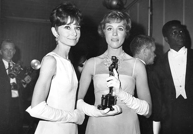 Julie Andrews, holding her Oscar statuette, poses with Audrey Hepburn backstage at the 37th annual Academy Awards ceremony at the Santa Monica Civic Auditorium in Santa Monica, Ca., April 5, 1965.