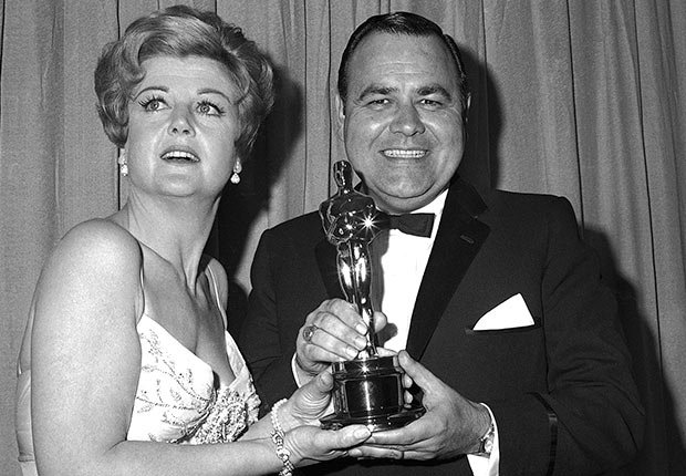 Comedian Jonathan Winters accepts Oscar won by Peter Ustinov as best supporting actor of the year, presented by actress Angela Lansbury, April 5, 1965.