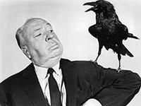 Alfred Hitchcock con un cuervo sobre su hombro izquierdo.