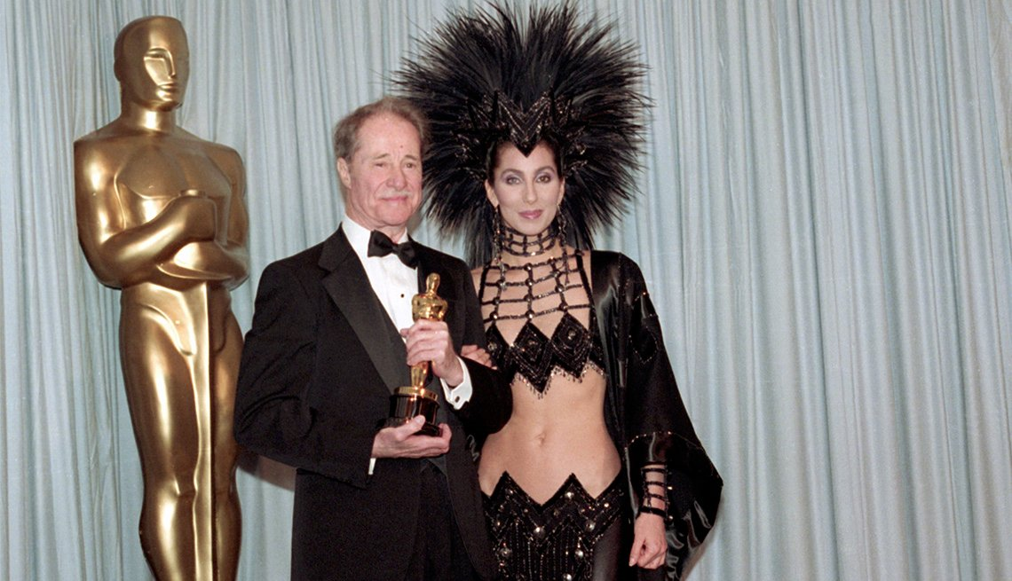 "item 9, Gallery image. Don Ameche, the winner for best supporting actor for ""Cocoon,"" and Cher, who had announced his category"