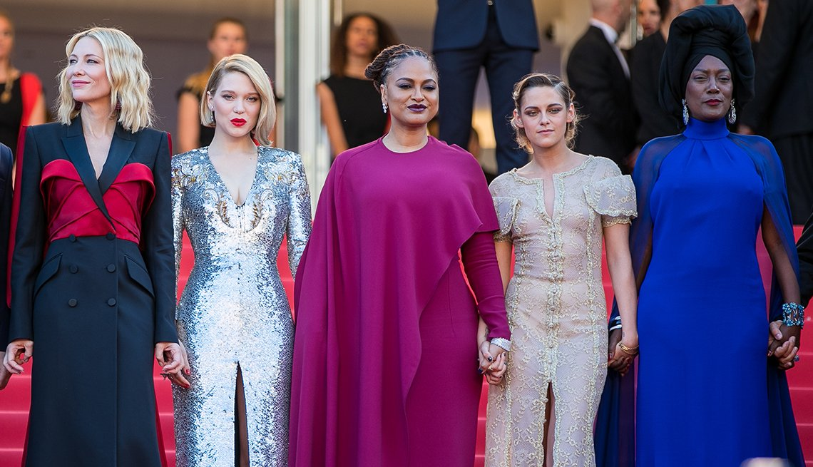 Five women holding hands on the red carpet at the 2018 Cannes Film Festival.