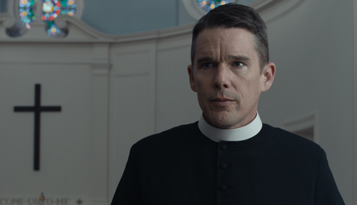 Ethan Hawke in a church with a cross in the background